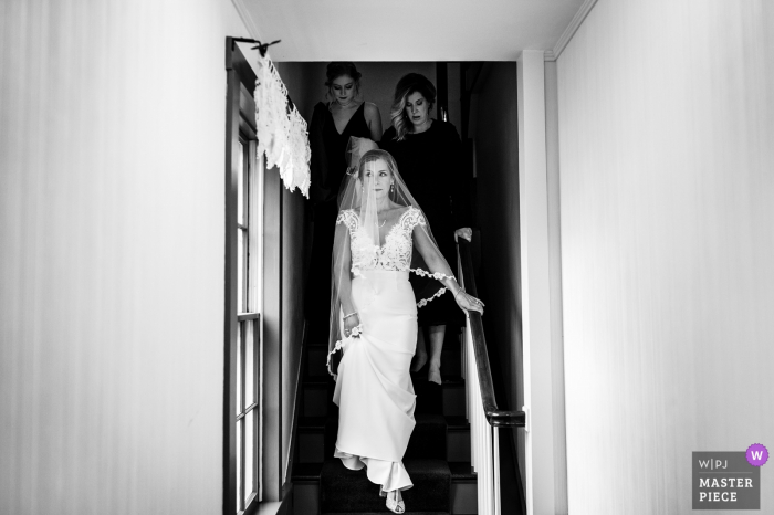 Venue photography on wedding day from Grafton Inn in Grafton, VT (getting ready location) - The bride walks down the stairs before the ceremony begins.