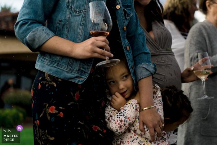 Photographe du lieu de mariage Benson Winery: un enfant se cache de la pluie sous le manteau de sa mère lors d'une cérémonie de mariage en plein air