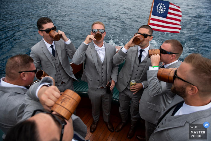 Lake Tahoe, California wedding photographs : Groom and Groomsmen toasting on a boat on way to ceremony.