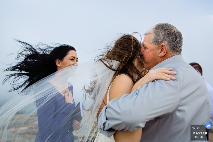Cadillac Mountain wedding photos - A father kisses the bride on a windy mountain in Maine