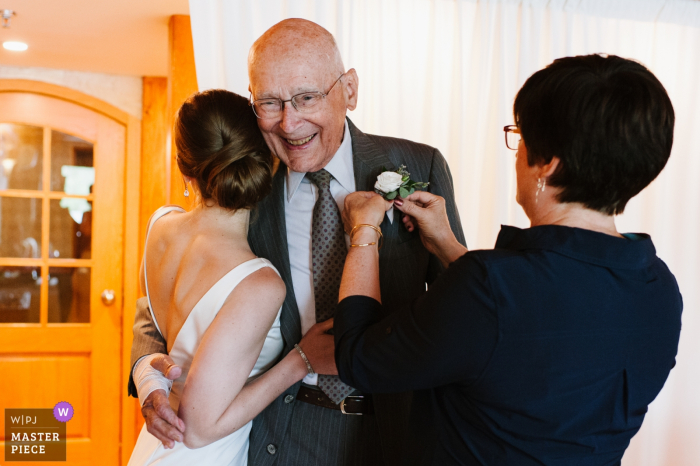 Photographe de mariage pour le Golden Arrow Lakeside Resort - Le grand-père de la mariée sourit alors qu'il est embrassé par la mariée et sa fille épinglant sa boutonnière.