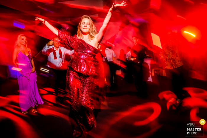 A girl in red in a red room dancing and enjoying the party at a Saint Tropez wedding.