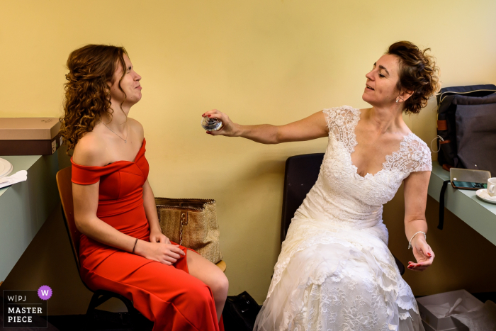 Getting Ready room photography - The bride sprays perfume on her daughter which does not really like the idea by the look of it