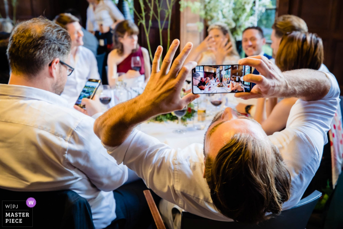 Landgoed Rhederoord dinner reception at the wedding. Guest taking photo of the bride and groom at the table.