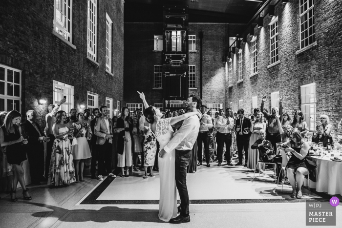 Hackney Town Hall, London wedding photographer: A couple perform their first dance in front of their family and friends