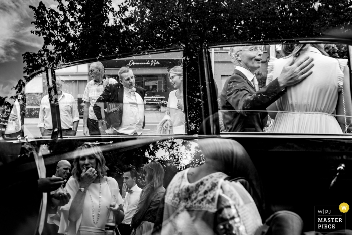 Black and white photo of a reflection of wedding guests on a car in Belgium.