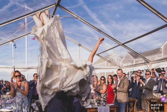 Great Harbor Yacht Club - Nantucket Island Wedding Photography | Groom picking Bride up just as they entered the tent for their reception and first dance.