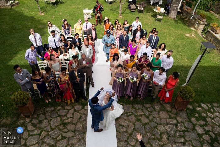 Umbria Italy Casa Bruciata resort outdoor wedding ceremony photo of the groom remove the veil of the bride
