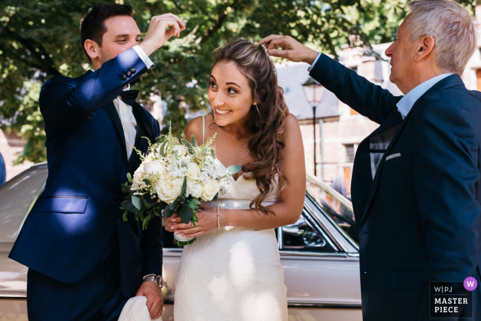 Flanders wedding photos outside the town hall   The groom and father of the bride clean the bride's hair which is covered with flower petals