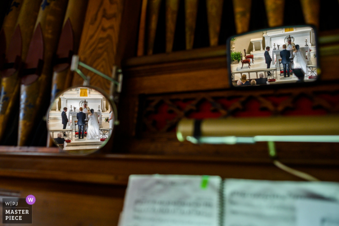 Charleston, SC wedding ceremony images | The organist's point of view of the ceremony with the bride and groom