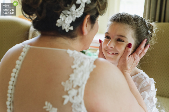 The Inn at Erlowest, Lake George, NY wedding venue image: A bride lovingly holds her flower girls face as they prepare for the wedding ceremony.