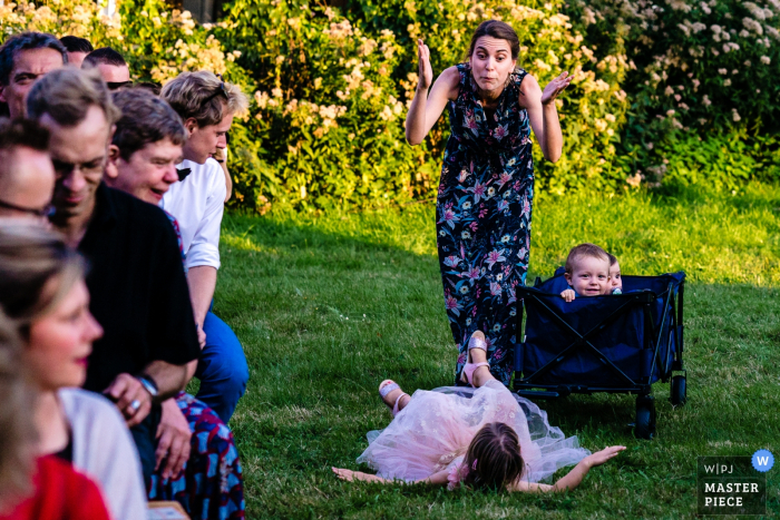 Flanders wedding photographer in Helecine- Poor Bride's maid helping children at outdoor ceremony