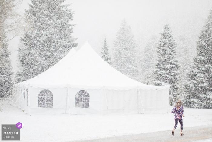 Victor, Idaho wedding image contains: A bridesmaid sprints through dumping snow