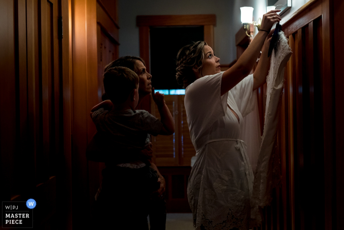 Rangely Maine wedding photographer: The bride gets her wedding dress down with her mom and son watching