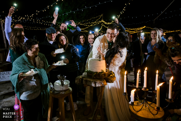 Bedouin Bar, Bulgaria wedding image contains: Cake cutting, kiss, hug, bride, groom, candles