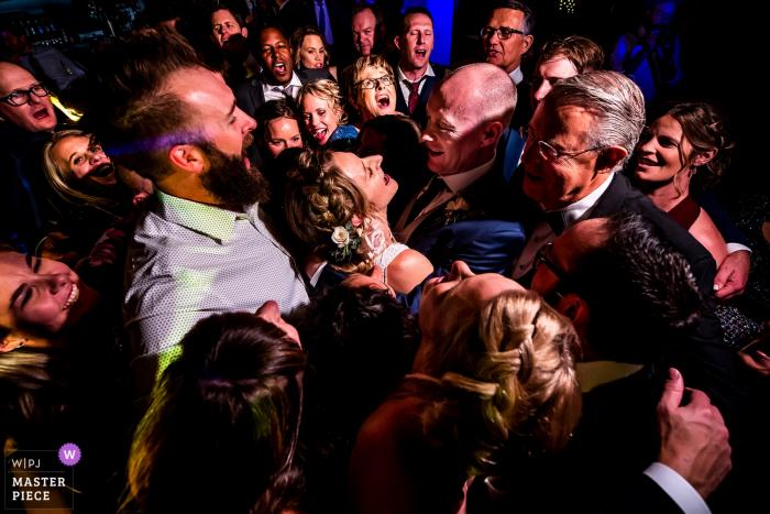 Ironworks (Denver, CO) wedding photographer: Bride and groom getting a group hug on the dance floor.