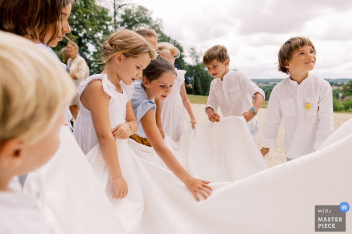 Chateau d'Azy wedding photography outside of Kids playing with the dress