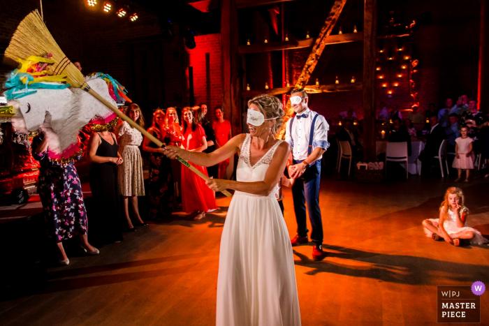Kasteel van Hoen wedding reception image of the bride with a broom hitting a pinata.