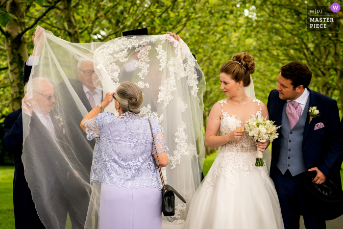 Flanders wedding photographer: I was taking the family photographs and the grandmother was explaining to all the grandfathers how they had to hold the wedding dress, just love the reactions on their faces and the way that grandmothers explains it