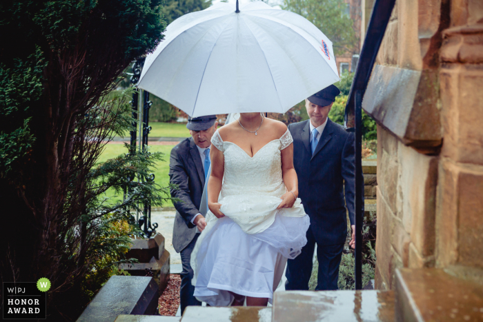 Stirlingshire wedding reportage photographer at a church in Scotland - Photo: Bride arrives during a downpour.
