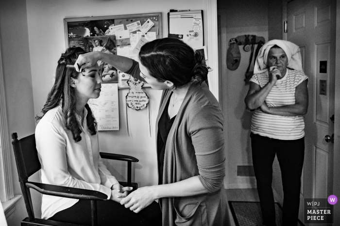 New York City wedding photographer captured a getting ready image of the bride having her makeup done.