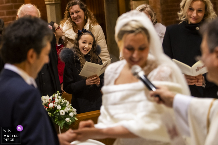 Milano wedding photography:  a bride speaks into a microphone during the ceremony as the witnesses watch with emotion.