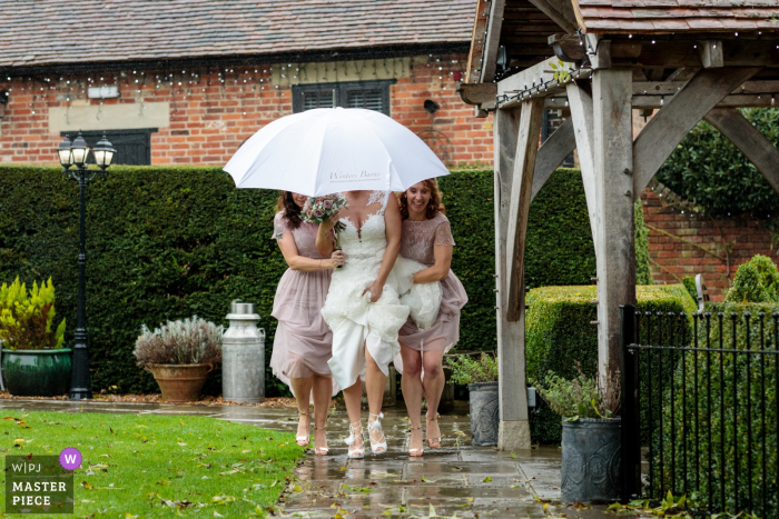 Wedding Reportage Image from Winters Barns, Canterbury, Kent, UK - The bride is escorted by her bridesmaids as they she makes her way to be married and dodges the rain
