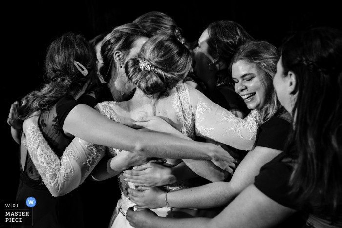 Flanders Reception Image Contains: The friends of the bride give her a group hug after their speech