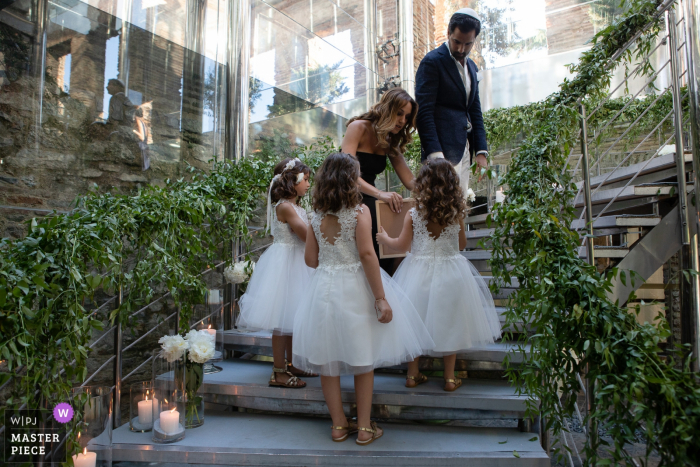 Turkey wedding ceremony image contains: A woman helps flower girls on the stairs leading to the ceremony