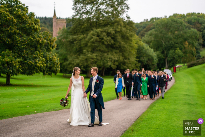 St Audries Park, Somerset, UK wedding image contains: Bride & Groom walking from their Church, in the background, towards their venue, with all their guests following