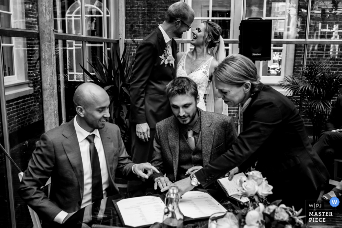 Amsterdam, The Netherlands	wedding image: While the best men is signing the wedding contract the bride and groom only have eye for each other