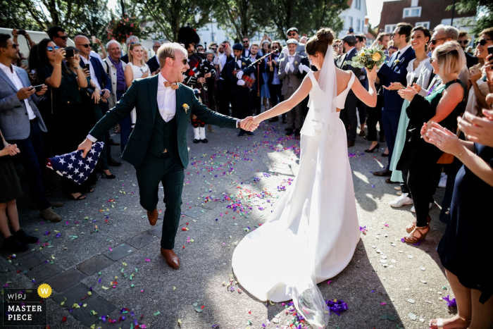 """Île-de-France wedding photo: Out of Church dancing bride and groom with sound of """"Scottish pipe"""""""