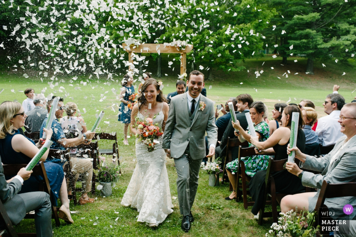 Glen Falls House, Round Top, NY wedding picture: A bride and groom joyfully recess the aisle at the end of their wedding ceremony while guests shoot confetti canons over them.