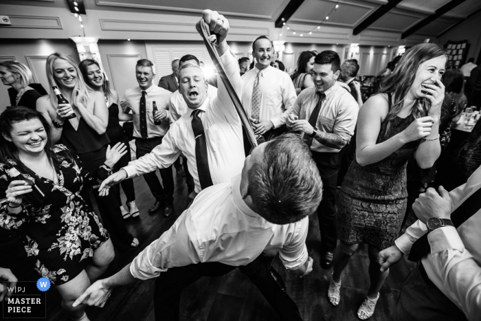 Wedding reception photography | Guest grabs tie of another guest on dance floor at Lake Mohawk Country Club, New Jersey