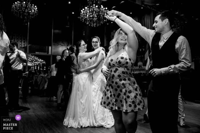 Wedding Event Photography at the Hotel 10, Montreal, Quebec - Brides dance together surrounded by their wedding guests dancing