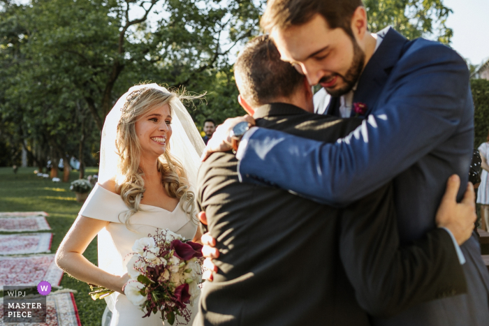 Bride thrilled to see father hugging groom at their Cachoerinha wedding