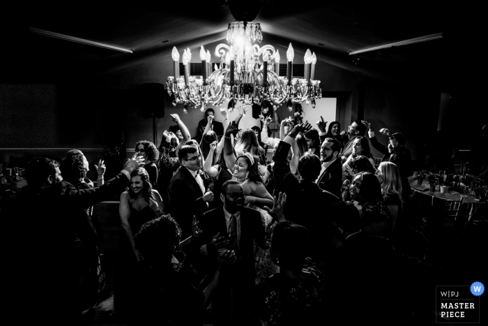 Top of the Town - Arlington VA - Wedding photo of the Bride & Groom in the center of a hectic dance floor with epic backlight