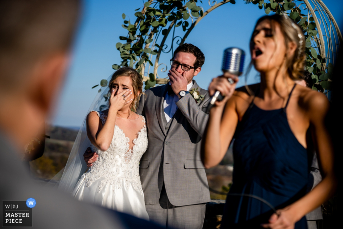 Wedding photographer for the Bluemont Vineyard, Virginia, USA   A talented bridesmaid sings a moving song to the bride and groom