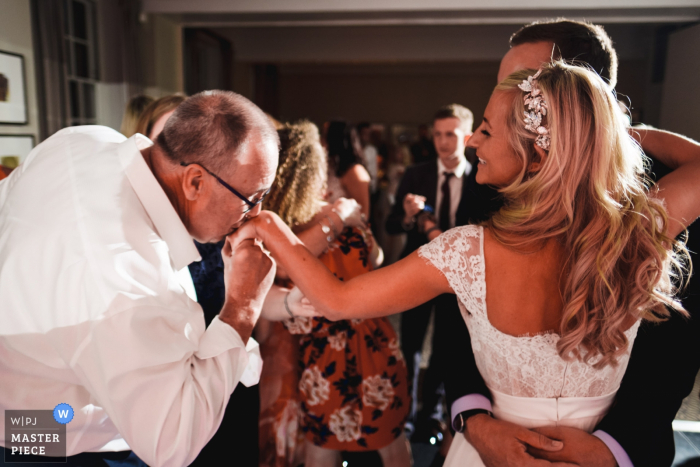 Devonport House, London wedding venue photography in reportage-style | Father kissing bride's hand on the dance floor