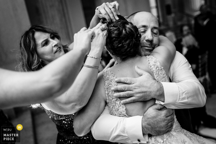 Reception Venue Photography | The bride making her rounds at the reception. She is hugging her Uncle as her Aunts work on fixing her hair.