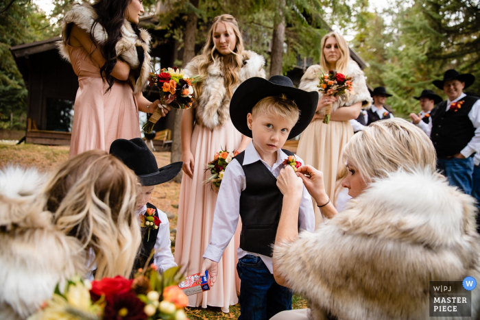 Priest Lake, Idaho photo of the ring bearer getting final preparation help by bridesmaids.