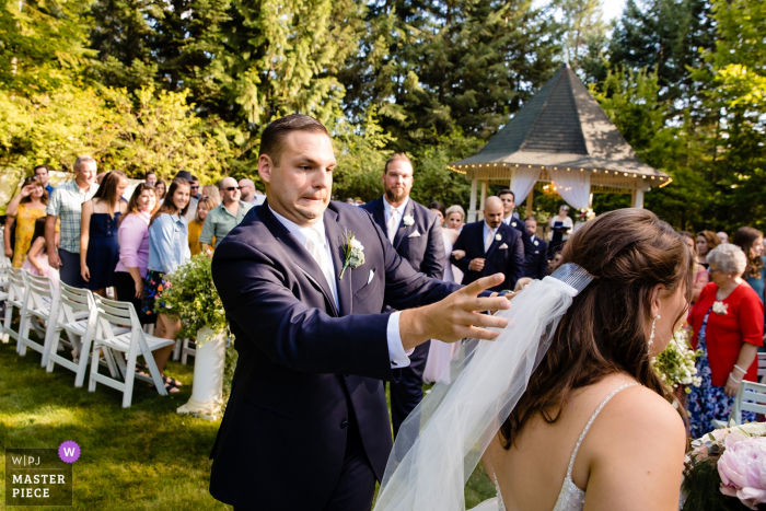 Chattaroy, Washington wedding pictures from outdoor ceremony | Groom reacts to his bride's veil falling out after the ceremony.