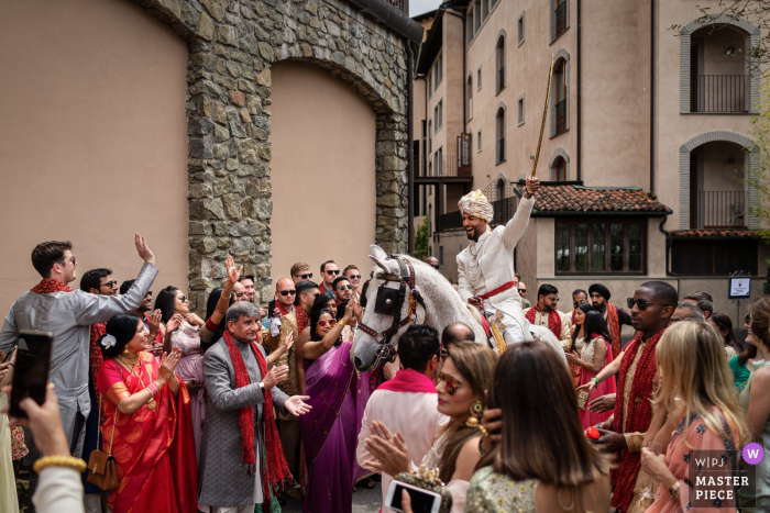 Tuscany Indian wedding traditions photography | The groom arrives on horseback with a sword overhead