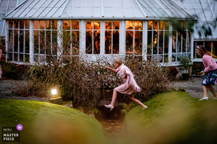 Glenapp Castle, Schottland Hochzeitsgäste während des Empfangs | Kinder verkleidet und springen die Lücke im Garten draußen.