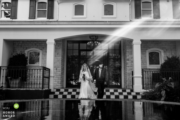 Western Capeoutdoor wedding Ceremony image showing The bride and her father 'walking down the isle' while a sun streak perfectly highlight the bride