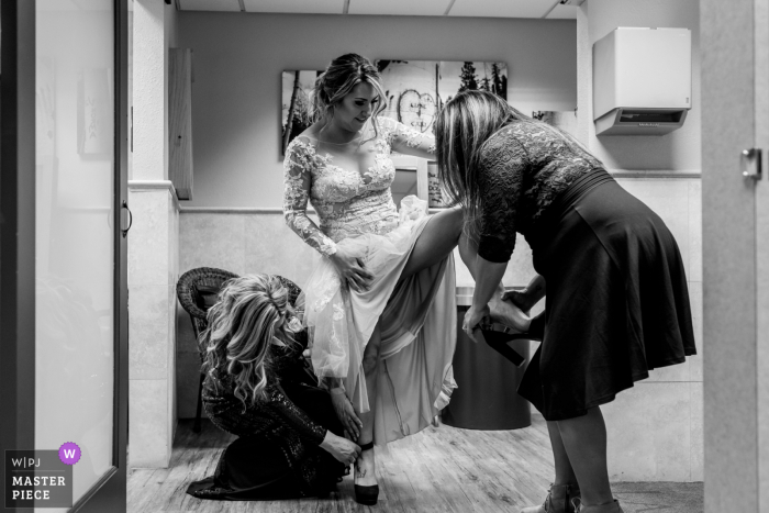 South Lake Tahoe, CA wedding image of a bride getting help with her shoes before her wedding