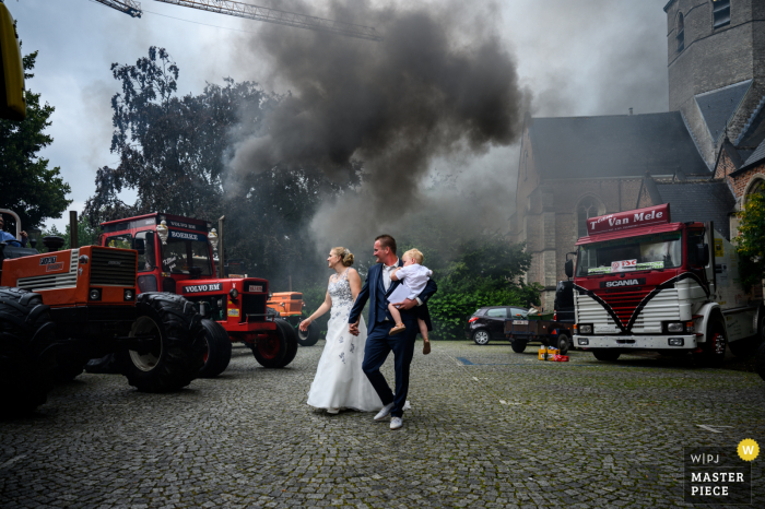 Stekene Church Wedding Image of the bride and groom leaving the area with a huge amount of black smoke exiting a tractor