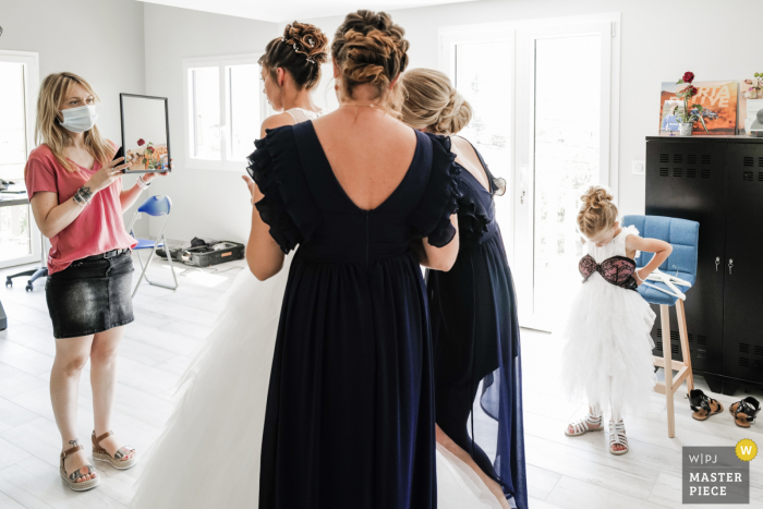French Wedding Photographer | the bride's daughter plays with her mom's bra while putting on the wedding dress