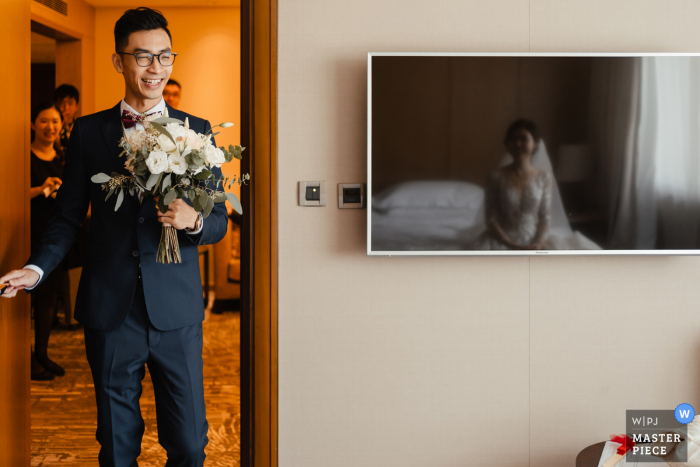 Taiwan Wedding Image at a hotel - the groom arrives at the bride's room with a bouquet of flowers.  The bride is reflected in the tv screen