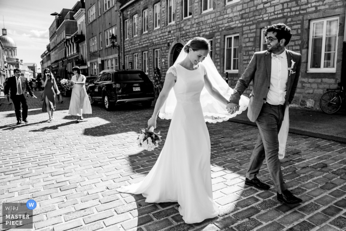 Canada wedding photography from Old Montreal of the couple walking hand in hand as guests follow behind them on the street